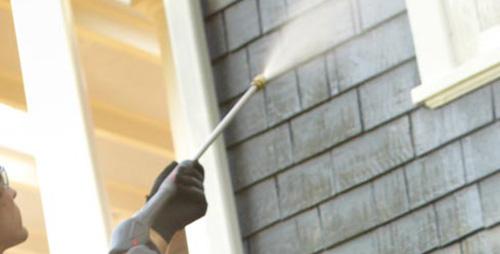 laborer pressure washing house